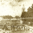 Church square showing members of the community gathering...late 19th century. Church is shown at right behind trees.